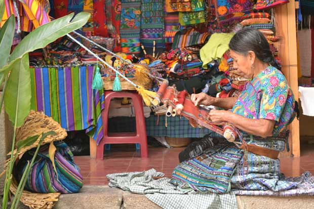 A weaver using backstrap loom in Antigua, Guatemala via Paint + Pattern