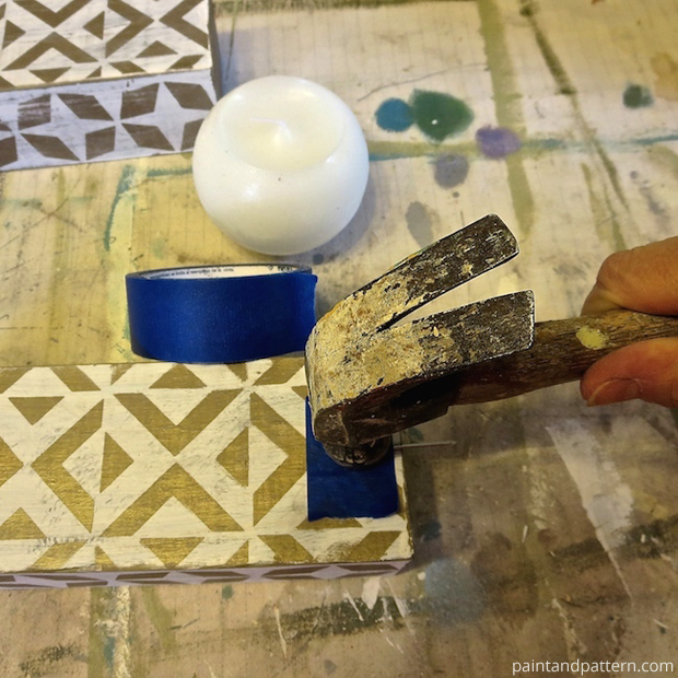 Denting the wooden piece with a nail for DIY Stenciled Chunky Candlesticks | Paint + Pattern