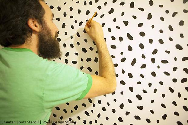 Joey Touching up the Finished Stencil Wall via Making a House a Home | Cheetah Spots Stencil by Royal Design Studio