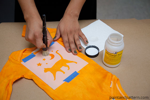 applying discharge paste to Halloween stenciled onesies